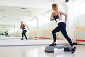 Back view of fitness instructor making step aerobics in gym. Sporty woman training step aerobics in gym  poster