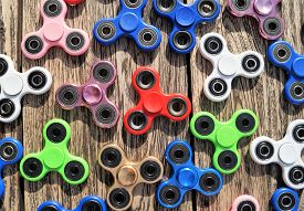 Fidget Spinners. Waterloo, Belgium - June 11, 2017. Assorted colorful fidget spinners on a rustic wood table. The popular hand spinner toys have become a worldwide trend.