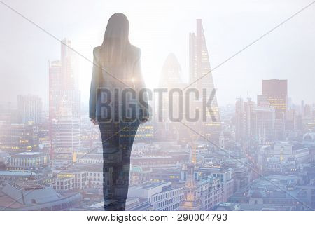 Young Woman Looking Over The City Of London Business Aria With Skyscrapers  At Sunset. Future, New B