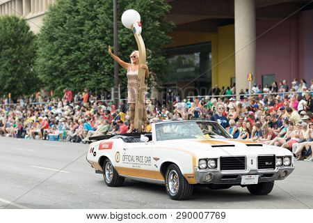Indianapolis, Indiana, USA - May 26, 2018, Linda Vaughn racing beauty queen, on top of a plataform on the back of a classic car, going down the street at the Indy 500 Parade
