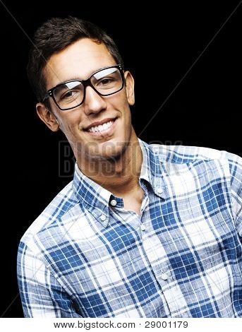 portrait of young student with glasses smiling over black background