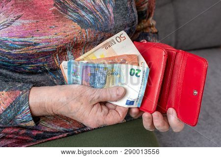 Hands Of An Elderly Pensioner Holding Leather Wallet With Euro Currency Money. Concept Of Financial