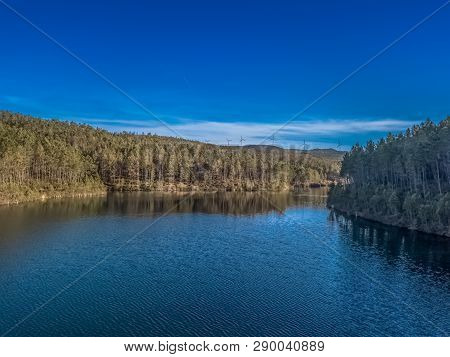 Aerial View Of Drone, Forest With Lake In Mountain With Wind Turbines On Ridge, In Portugal