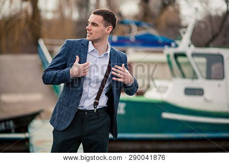 Young Man Businessman In Jacket Stands On Pier Against Boat Background