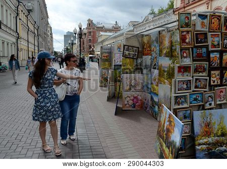 Moscow, Russia - June 21, 2018: Unknown Tourists Watch Art Paintings On The Pedestrian Arbat Street