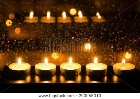 Candles Reflected In The A Wet Window