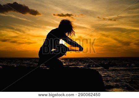 Feminine Silhouette On The Gold Sunset Background