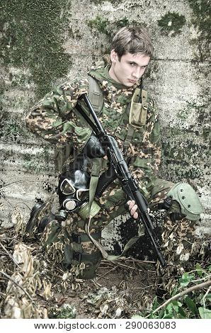 Soldier With A Rifle Hiding Behind An Old Concrete Wall Strengthening