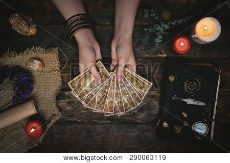 Tarot Cards, Magic Book And Fortune Teller Hands On A Wooden Table Background. Future Reading Concep