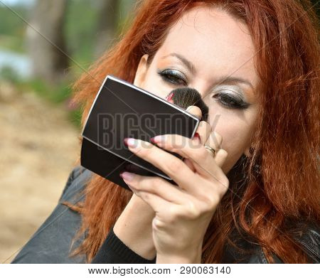 Red-haired Woman Putting On Makeup While Looking In A Small Mirror