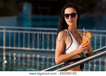 Attractive Young Slim Woman With Long Dark Hair At The Swimming Pool Entrance Holding A Cocktail Wea