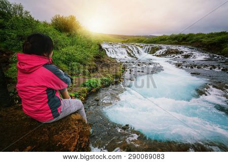 Woman Traveler Travels In Landscape Of Bruarfoss Waterfall In Brekkuskogur, Iceland. Bruarfoss Water