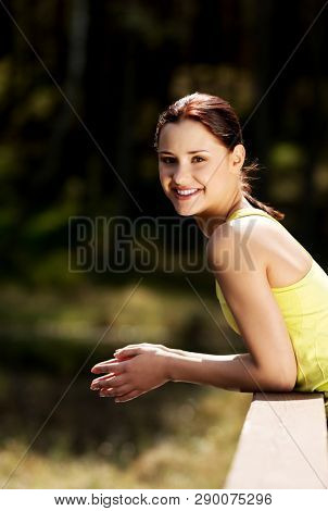 Young smiling woman resting in forest in sunny day. Outdoor activity.