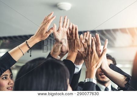 Many Happy Business People Raise Hands Together.