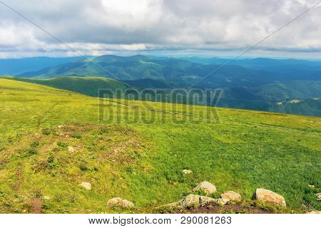 Mountain Landscape In Summer With Cloudy Sky. Green Grassy Meadow With Some Rocks On The Hill. Ridge