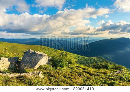 Mountain Landscape In Summer With Cloudy Sky In Evening. Green Grassy Meadow With Some Rocks On The