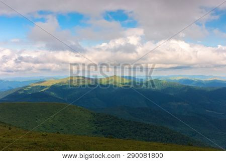 Mountain Landscape With Cloudy Sky. Peaks Of Distant Ridge In Sunlight. Beautiful Scenery After The