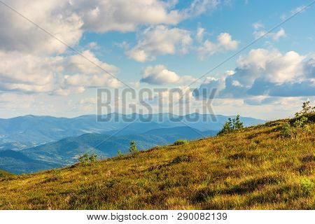 Mountain Scenery In Summer Afternoon. Fluffy Clouds On A Blue Sky Above The Distant Ridge. Grassy Al