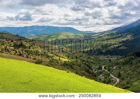 Mountainous Countryside In Springtime. Village In The Valley, Rural Fields On Hills. Distant Mountai