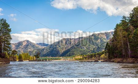 Panoramic View On Mountain River With Bridge In Front Of Mountain Range, National Park In Altai Repu
