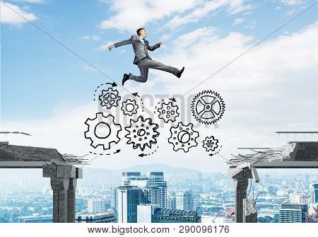 Businessman Jumping Over Gap With Gear Mechanism In Concrete Bridge As Symbol Of Overcoming Challeng