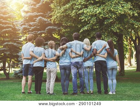 Volunteering And Ecology. Group Of Millennials Volunteers Embracing In Park, Back View, Empty Space
