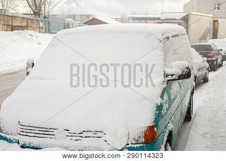 Green Car Is Covered With Snow Parked Near The Street