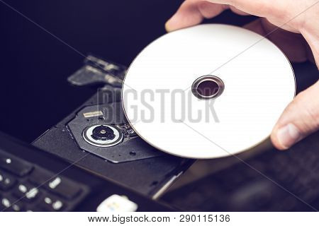 Male Hand Inserting A Dvd Into A Disk Drive. Software Or Drivers Installation Concept.