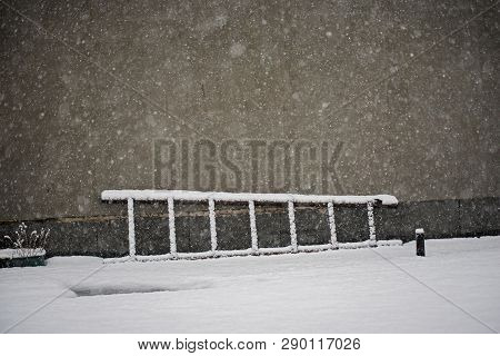 Old Wooden Ladder Laying On The Snow Near The Wall.