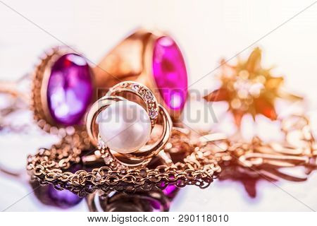 Elegant Luxury Composition Of Gold Jewelry With Pearl Ring, Amethysts And Rubys Gemstones On Light B