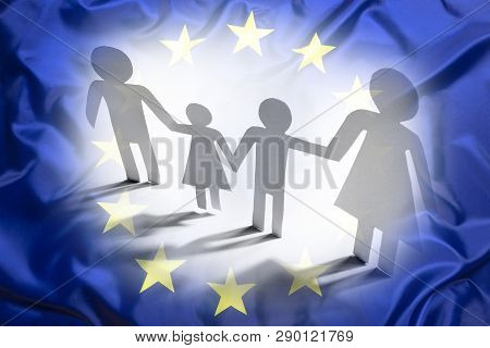 Family With Two Children In Europe, Paper Figures With European Flag As Background