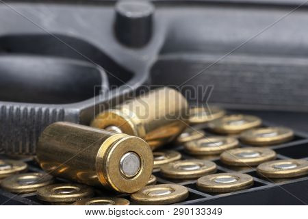Pistol And Bullets Close-up Isolated On White Background. The Concept Of Limiting The Spread Of Smal