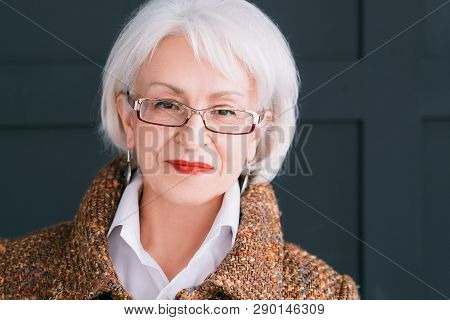 Senior Fashion Model Portrait. Modern Lifestyle. Stylish Aged Woman In Autumn Outfit Looking At Came