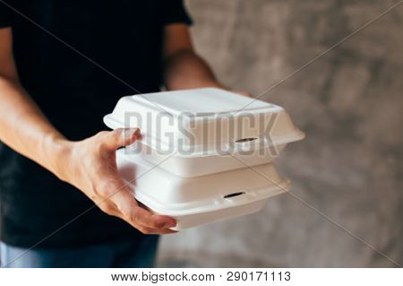 Close-up Of Delivery Man Handing A Slack Of Foam Lunch Box - Foam Box Is Toxic Plastic Waste. Used F