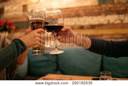 Friends In A Restaurant Toasting Beer And Wine. Three Friends In Restaurant Celebrating. Evening Go