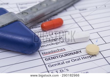 Neurological reflex hammer and colored tablets, pills and capsula lies on a sheet of health history with the words neurological headaches. Treatment of neurological diseases, accompanied by headache poster