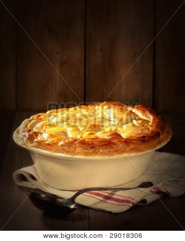 Game pie in serving dish on rustic background with spoon