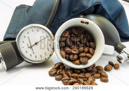 Coffee And Blood Pressure. Cup With Coffee Beans Inside, Surrounded By Cuff And Sphygmomanometer For