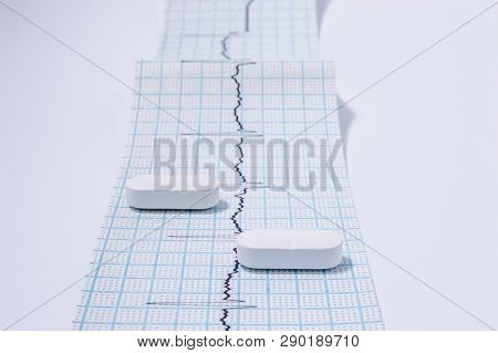 White Oblong Pills Or Tablets Are On The Tape With Ambulatory Electrocardiogram (ekg Or Ecg) Records