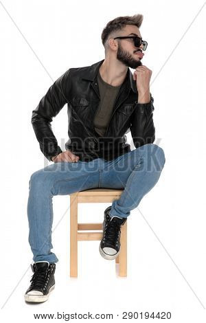 man in black jacket and blue jeans sitting on chair thinking while being goofy with tongue out on white background