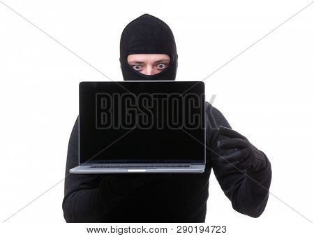 Hacker man in black mask with laptop with blank screen in hands.