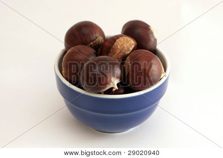 Bowl full of chestnuts on white background (horizontal)