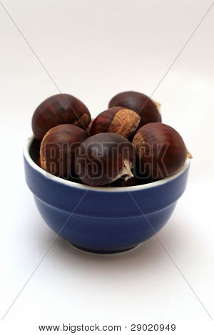 Bowl full of chestnuts on white (vertical)