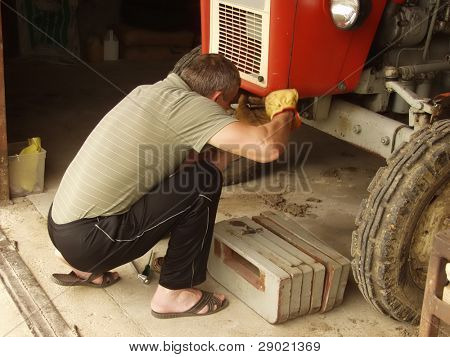 Man repairs a tractor