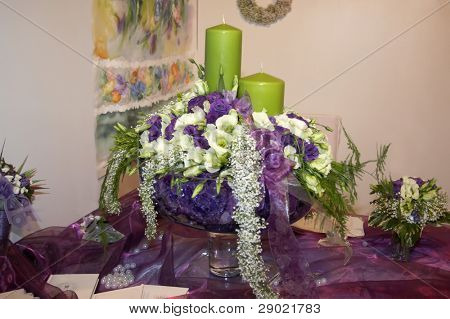 Flower arrangement with two green candles