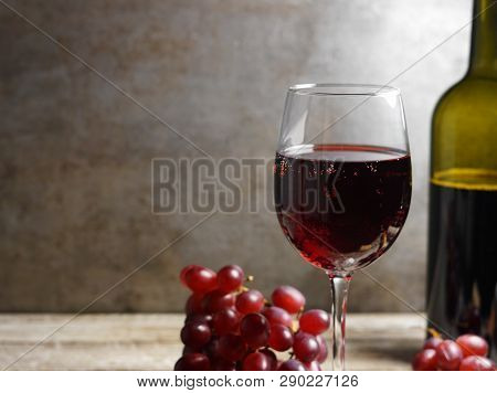 Glass Of Red Wine On A Wooden Table In A Rustic And Vintage Wine Bar With Grapes Fruit And A Bottle