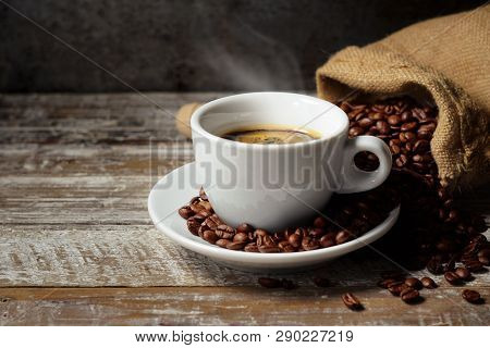 Coffee Cup And Roasted Coffee Beans In A Burlap Sack On A Rustic Wooden Table On Rusty Vintage Backg