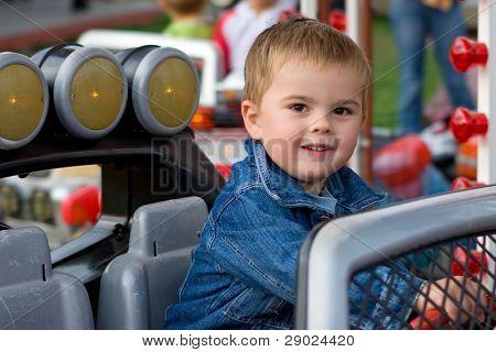 hübsch kinder kleinkind junge Reiten ein Auto auf eine merry Go round und lächelnd