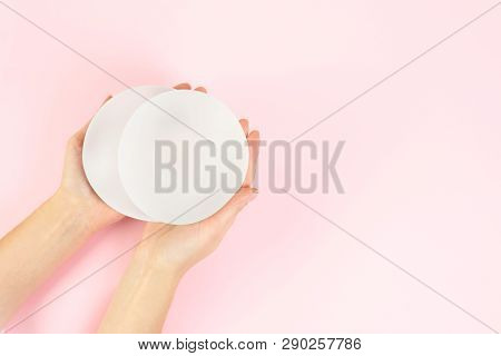 Woman Holding Silicone Implants For Breast Augmentation On Color Background, Top View With Space For