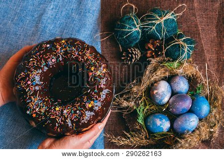 Woman Holding Chocolate Cake With Powder Next To Space Galactic Easter Eggs In Nest Next To Bump And